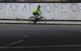 A cyclist passes graffiti in London on Monday, April 13, 2020. (AP/Kirsty Wigglesworth)