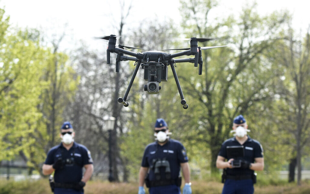 Police officers prepare a drone to find residents who fail to comply with the stay-at-home order implemented due to the coronavirus pandemic in Szolnok, Hungary, April 13, 2020. (Janos Meszaros/MTI via AP)