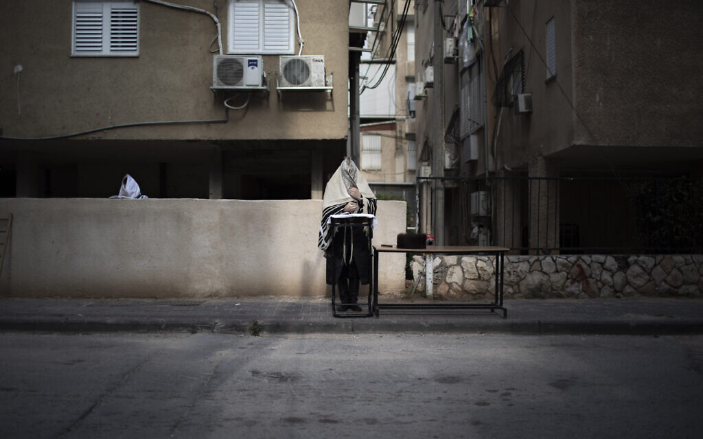 Ultra-Orthodox men pray the morning prayer next to their house as synagogues are closed following the government's measures to help stop the spread of the coronavirus, in Bnei Brak,  April 14, 2020. (AP Photo/Oded Balilty)