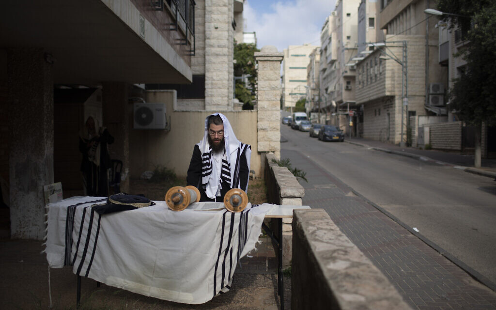 An ultra-Orthodox Jew prays next to his house as synagogues are closed following the government's measures to help stop the spread of the coronavirus, in Bnei Brak,  April 14, 2020. (AP Photo/Oded Balilty)