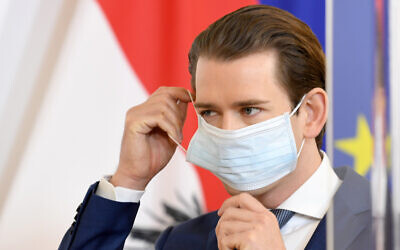 Austrian Chancellor Sebastian Kurz wears a protective mask as he arrives for a coronavirus press conference in Vienna, Austria, April 14, 2020. (Roland Schlager/APA via AP, Pool)