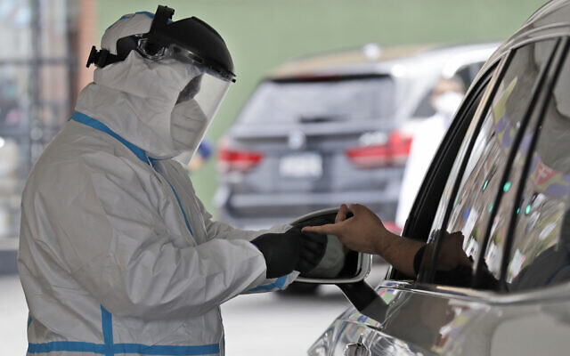 A man's blood is collected for testing of coronavirus antibodies at a drive through testing site in Hempstead, New York, April 14, 2020. (AP Photo/Seth Wenig)
