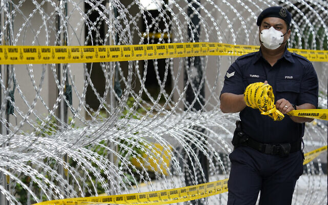 A police officer sets up perimeter at a building under lockdown in Kuala Lumpur, Malaysia, April 15, 2020. (AP/Vincent Thian)
