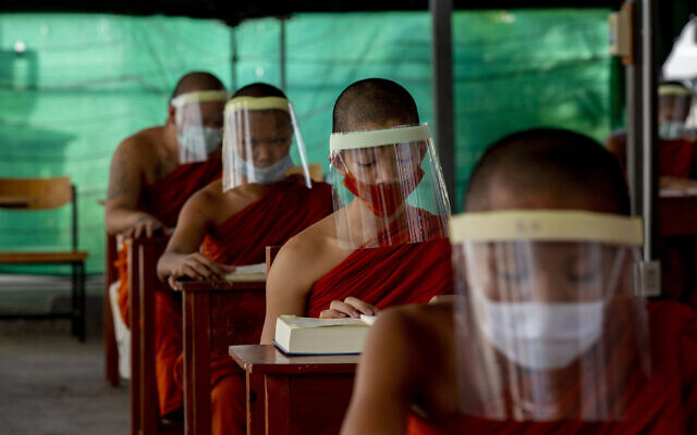 Novice Buddhist monks with protective masks and face shields, seated maintaining social distancing participate in a religious class at Molilokayaram Educational Institute in Bangkok, Thailand,  April 15, 2020. (AP Photo/Gemunu Amarasinghe)