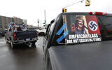 Signs showing Gov. Gretchen Whitmer are taped to vehicles during a protest in Lansing, Michigan, April 15, 2020 (AP/Paul Sancya)