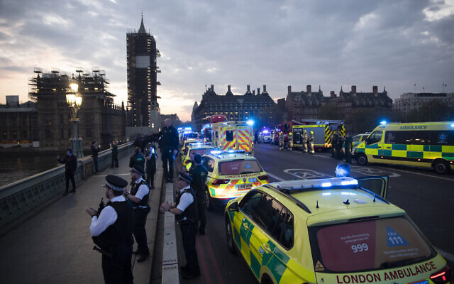 "London Ambulance staff, police officers and firefighters take part in the weekly ""clap for our carers"" as they stand on Westminster Bridge backdropped by a scaffolded Big Ben and the Houses of Parliament in London, during the lockdown to try and stop the spread of the coronavirus,  April 16, 2020. (AP Photo/Matt Dunham)"