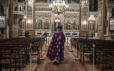 In this April 13, 2020, photo a priest takes part in a Holy Monday ceremony held without worshipers at the Athens Cathedral, in Greece, during a lockdown order by the government to prevent the spread of the coronavirus (AP Photo/Petros Giannakouris)