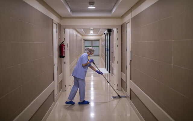 In this April 16, 2020 photo, a staffer disinfects an alley of the Clinica CEMTRO in Madrid, Spain. (AP Photo/Bernat Armangue)
