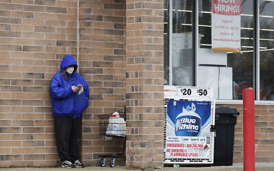 A woman checks her phone as a hiring sign shows at a Family Dollar store in Illinois, April 17, 2020. (AP Photo/Nam Y. Huh)