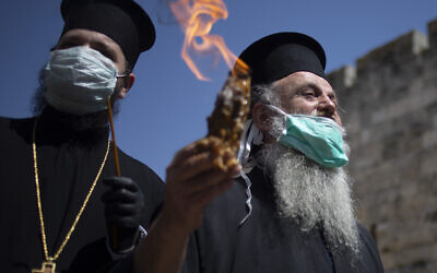 An Orthodox clergyman holds the holy fire to transfer to predominantly Orthodox countries from the Church of the Holy Sepulchre, traditionally believed by many Christians to be the site of the crucifixion and burial of Jesus Christ, in Jerusalem's old city after the traditional Holy Fire ceremony was called off amid the coronavirus, April 18, 2020. (AP Photo/Ariel Schalit)