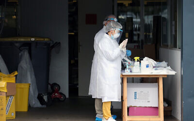 Medical staff prepare to test people in their cars with COVID-19 symptoms, at a drive-through testing site outside a medical biology laboratory in Anglet, southwestern France, April 20, 2020. (Bob Edme/AP)