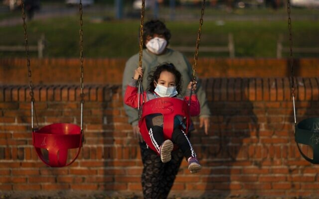 Illustrative: A child wearing a mask to prevent the spread of coronavirus is pushed in a swing by a woman in Montevideo, Uruguay, April 23, 2020.(AP Photo/Matilde Campodonico)