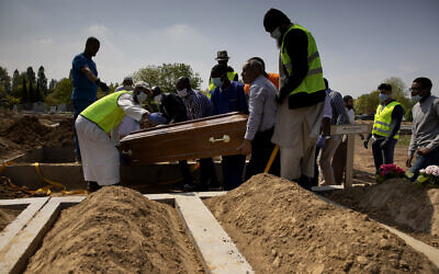 Mourners set down the coffin of a Guinean man who died of COVID-19 during a funeral at the cemetery of Evere, Belgium, Friday, April 24, 2020 (AP Photo/Virginia Mayo)