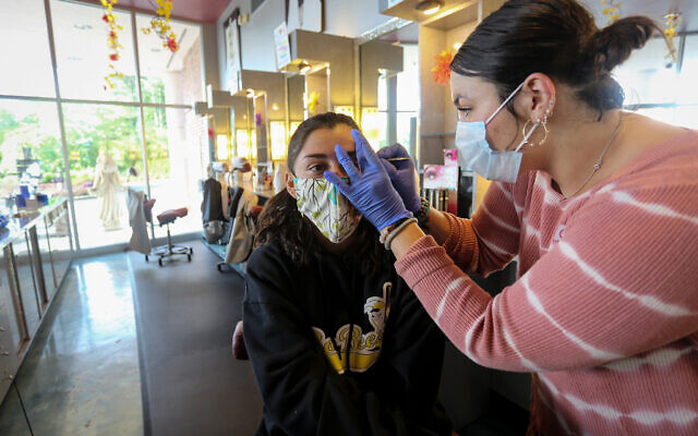A customer gets her eyebrows waxed at Three-13 Salon, Spa & Boutique on Friday, April 24, 2020, in Marietta, Georgia. The salon had been closed for more than a month due to the new coronavirus. (AP Photo/Ron Harris)