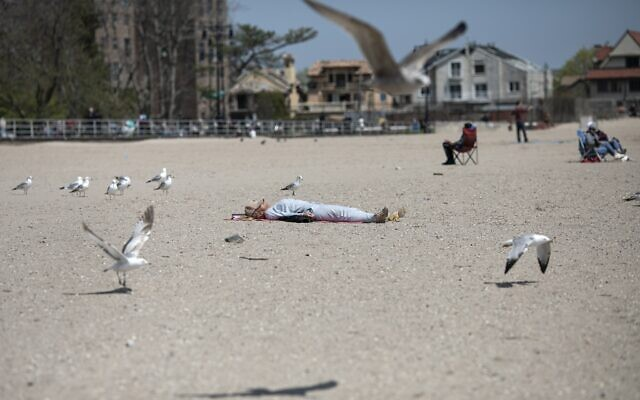 A woman sleeps on Brighton Beach in the Brooklyn borough of New York as seagulls flutter around her, on Saturday, April 25, 2020. (AP/Wong Maye-E)