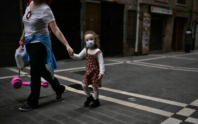 Irati, a little girl, 3 years old, wears face mask to prevent the coronavirus while she's going for a walk with her mother, Montse Fernandez , in Pamplona, northern Spain, Sunday, April 27, 2020.  (AP Photo/Alvaro Barrientos)