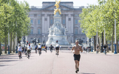 A runner on the Mall in central London, where the finish of the London Marathon course would be, which was postponed to help curb the spread of the coronavirus, Sunday April 26, 2020. (Dominic Lipinski/PA via AP)