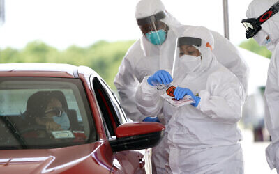 Registered nurse April Lewis, center, prepares to administer a test at a newly opened United Memorial Medical Center COVID-19 drive-thru testing site, April 27, 2020, in Houston. (AP/David J. Phillip)