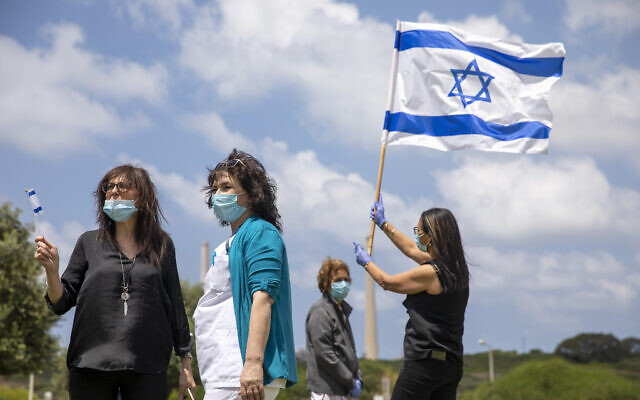 Medical staff and patients wear masks and wave Israeli flags as an Israeli Air Force aerobatic team flies in formation over the Hillel Yaffe Medical Center, in the northern city of Hadera, April 29, 2020. (Ariel Schalit/AP)