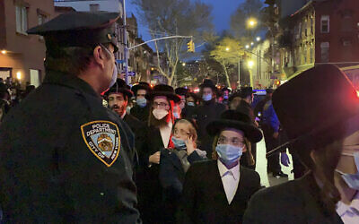A New York City police officer keeps watch as hundreds of mourners gather in the Brooklyn borough of New York, Tuesday, April 28, 2020, to observe a funeral for Rabbi Chaim Mertz, a Hasidic Orthodox leader whose death was reportedly tied to the coronavirus. (Peter Gerber via AP)
