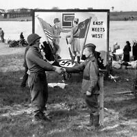 A soldier with the 1st US Army shakes hands with a Soviet counterpart, emulating the 'East Meets West' sign in the background, during the historic meeting of Allied fronts, by the river Elbe at Torgau, Germany, April 26, 1945. (AP/William C. Allen)