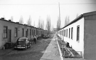 Refugees from former German territories live in the once notorious Dachau camp on March 10, 1954. Cars parked in Barracks Street give testimony of wealth achieved by some refugees. (AP Photo/Heinrich Sanden, Sr.)