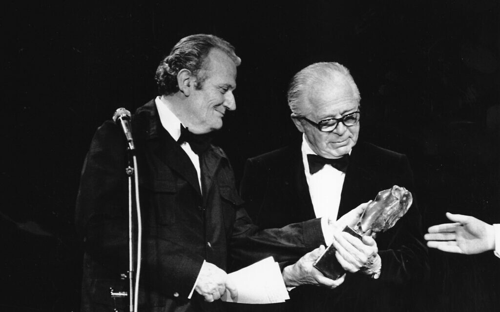 Writer Paul Guimard, French President Francois Mitterrand's special representative, is seen presenting a trophy to American director Billy Wilder (right) during the opening night ceremony of the 35th Cannes International Film Festival in Cannes, France, on May 14, 1982. (AP Photo)