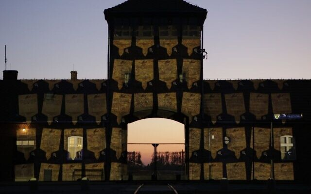 Virtual memorial plaques are projected on the gates of Auschwitz-Birkenau for Holocaust Remembrance Day, April 20, 2020. (Marcin Kozlowski/March of the Living)