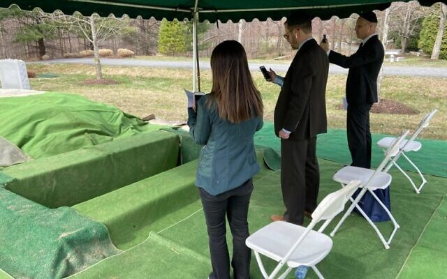Karen, Mark and Ken Katz bury their mother, Linda Katz, at the Garden of Remembrance in Clarksburg, Maryland, during a Zoom-conducted service on March 23, 2020. (Courtesy Garden of Remembrance Memorial Park)