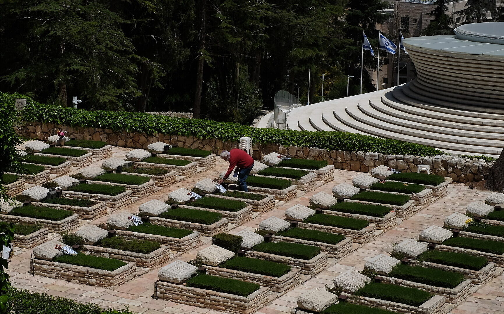 Chaim Frenkel puts a flower and a note on a grave on Mount Herzl in Jerusalem ahead of next week's Memorial Day, on April 23, 2020. (Judah Ari Gross/Times of Israel)