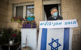 Illustrative: Joseph Kleinman, a 90-year-old Holocaust survivor who survived Auschwitz and Dachau Nazi death camp wearing a face mask and holding an Israeli flag at his porch in Jerusalem, during the Holocaust Remembrance Day, April 21, 2020. (Yonatan Sindel/Flash90)