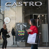 "File: People walk past black friday advertisements at an outlet of the ""Castro"" fashion chain in Jerusalem, November 24, 2019 (Olivier Fitoussi/Flash90)"