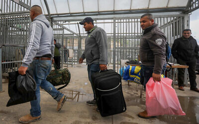 Palestinian workers from the West Bank city of Hebron carry personal belongings as they arrive at the Tarqumiya checkpoint to cross into Israel on March 18, 2020. (Wisam Hashlamoun/Flash90)