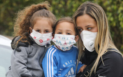 A family wear face masks to protect themselves from the coronavirus, March 18, 2020. (Yossi Aloni/Flash90)