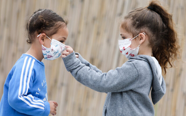 Illustrative: A family wears face masks for fear of the coronavirus, on March 18, 2020. (Yossi Aloni/Flash90)