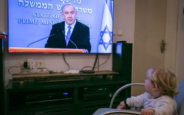 An Israeli child watch as Israeli prime minister Benjamin Netanyahu holds a live press conference on the new government restrictions for the public regarding the coronavirus COVID-19 on March 19, 2020. (Chen Leopold/Flash90)