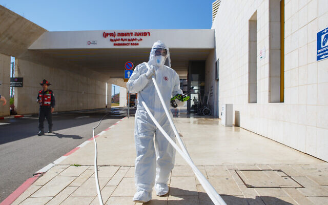 Firefighters wearing protective clothes disinfect Assuta hospital in Ashdod, on March 22, 2020 (Flash90)