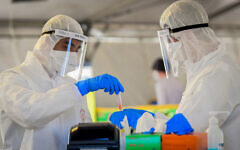 Magen David Adom medical team members, wearing protective gear, handle a coronavirus test sample at a drive-through site in Tel Aviv, March 22, 2020. (Flash90)