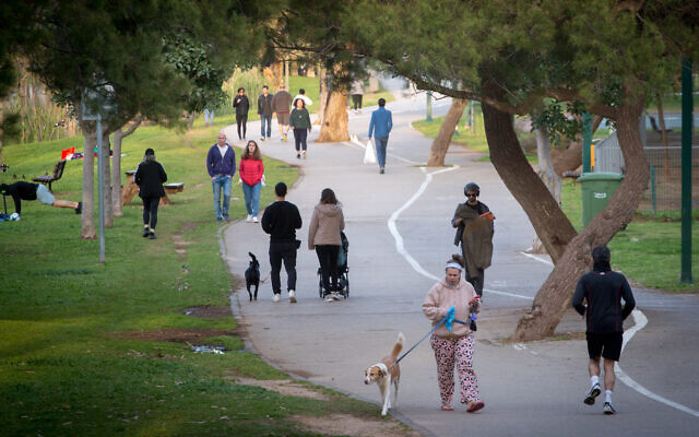 Israelis walk their dogs and exercise in  Tel Aviv's Yarkon Park on March 22, 2020, as the government issued instructions to avoid public spaces to prevent the spread of the coronavirus (Miriam Alster/Flash90)