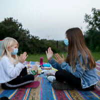 Children wearing face masks in a field at Hasharon Park, in Hadera, on March 23, 2020. (Chen Leopold/Flash90)