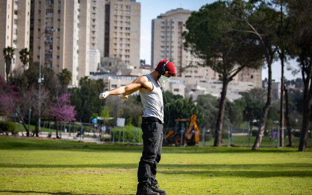 A man wearing a face mask exercises in the Saker Park in Jerusalem, on March 25, 2020. (Olivier Fitoussi/Flash90)