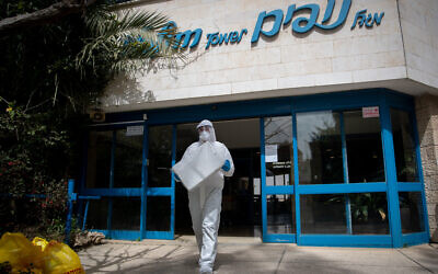 Magen David Adom worker wearing protective clothing tests residents of the Nofim Tower assisted living facility for coronavirus in Jerusalem on March 27, 2020 (Yonatan Sindel/Flash90)