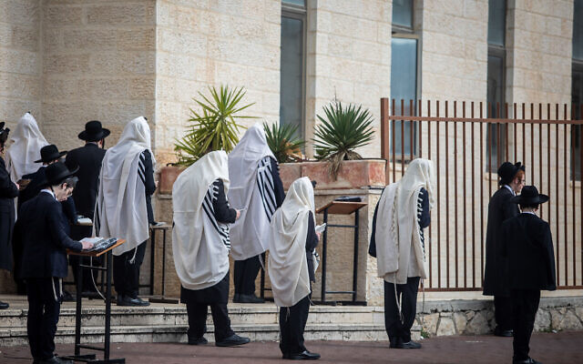 Illustrative: Jewish men pray outside a synagogue in the city of Beitar Illit, in the West Bank, March 29, 2020 (Aharon Krohn/Flash90)