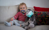 A baby girl plays with a masked monkey in Tel Aviv on March 29, 2020. (Miriam Alster/Flash90)