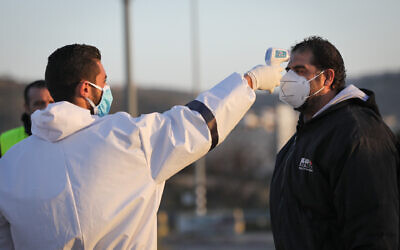 Palestinian medical employees disinfect Palestinian workers who came back from working in Israel at the entrance to the West Bank village of Hussan, on March 29, 2020 (Nati Shohat/Flash90)