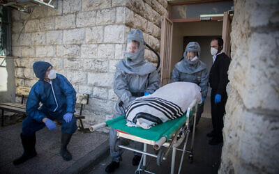 Illustrative: Chevra Kadisha workers wearing protective clothes carry the body of a patient who died from complications of COVID-19 at the Shamgar Funeral Home in Jerusalem, March 29, 2020. (Yonatan Sindel/Flash90)