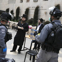 Illustrative: Police officers at a synagogue in the ultra-Orthodox neighborhood of Mea Shearim in Jerusalem as they close shops and disperse public gatherings for violating emergency directives against the coronavirus, March 30, 2020. (Olivier Fitoussi/Flash90)