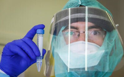 A lab technician carries out a coronavirus test at Rambam Medical Center in Haifa on March 30, 2020. (Yossi Aloni/Flash90)