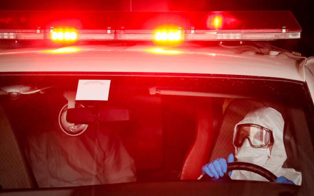 Magen David Adom workers wearing protective clothing as a preventive measure evacuating a man suspected of having coronavirus to Shaarei Tsedek hospital in Jerusalem, March 30, 2020. (Yossi Zamir/Flash90)