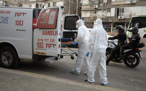 An illustrative photo of Magen David Adom paramedics transferring a man suspected of carrying the virus to an ambulance in the Tel Aviv suburb of Bnei Brak, March 31, 2020. (Gili Yaari/Flash90)
